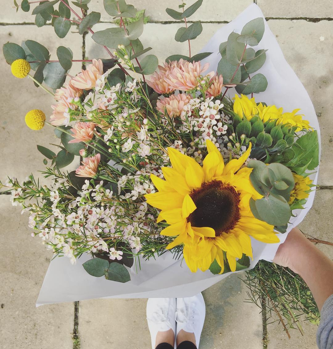 Stay wild flower child 🌺 Today's Posy is lush sunflowers, with billy buttons, lilac wax, dusty pink sprays, and fresh gum. Order before 12:30pm for delivery this afternoon 🌿Link in bio.
